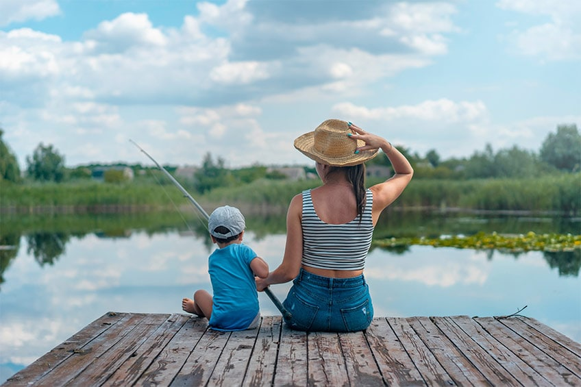 mom and son fishing on a dock