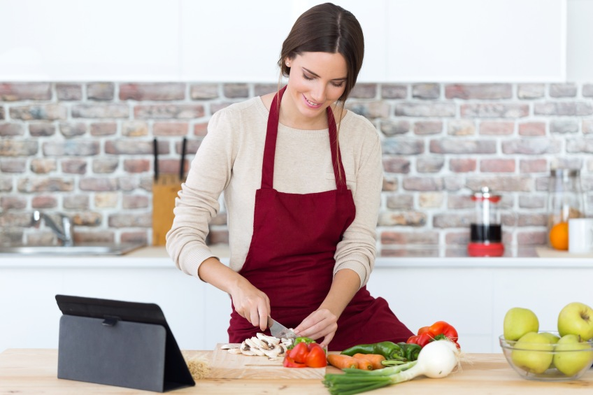 woman cooking in kitchen watching ipad